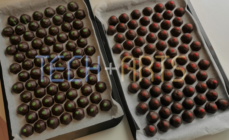 Finished chocolates on trays, with red and green dots to distinguish between flavours